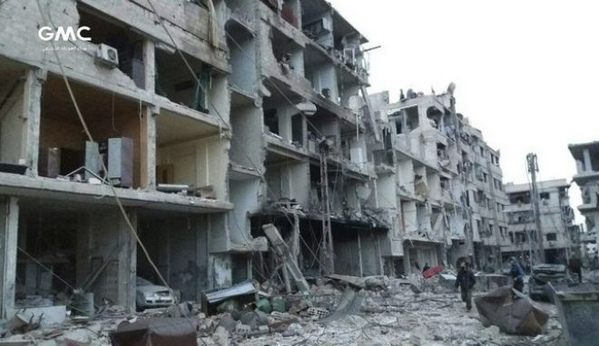 This photo released on Friday, Feb. 23, 2018 by the Syrian anti-government activist group Ghouta Media Center, which has been authenticated based on its contents and other AP reporting, shows Syrians walk between destroyed buildings during airstrikes and shelling by Syrian government forces, in Ghouta, a suburb of Damascus, Syria. Syrian government warplanes supported by Russia continued their relentless bombardment of the rebel-controlled eastern suburbs of Damascus for a sixth day Friday, killing five people, opposition activists and a war monitor reported. The death toll from the past week climbed to more than 400. (Ghouta Media Center via AP)