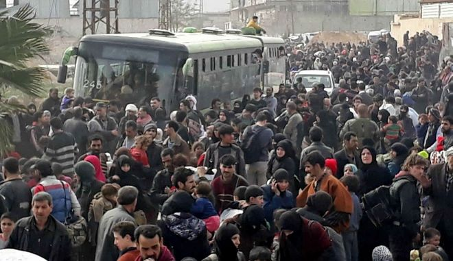 This photo released by the Syrian official news agency SANA, shows Syrian civilians with their belongings, fleeing from fighting between the Syrian government forces and rebels, in eastern Ghouta, a suburb of Damascus, Syria, Thursday, March. 15, 2018. Thousands of civilians streamed out of Hamouria in Syria's besieged, opposition-held enclave of eastern Ghouta on Thursday, crossing on foot and in pick-up trucks and tractors to government-held territory near the capital, Damascus, according to footage on state-run Syrian television. (SANA via AP)