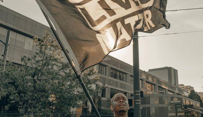 Άνδρας κρατάει σημαία Black Lives Matter