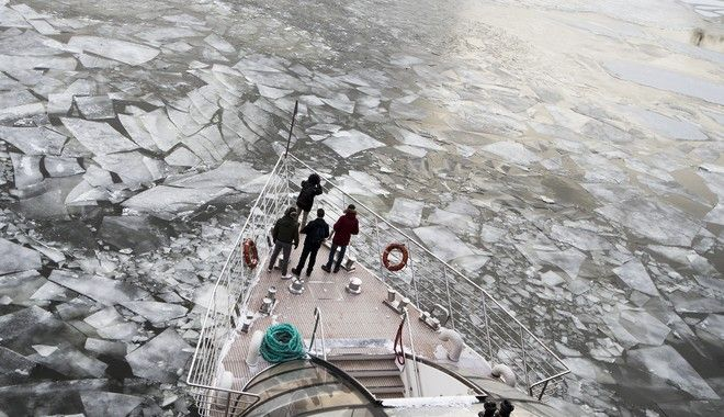 Passengers stand on a deck of a  tourist boat with restaurant aboard especially designed for winter river cruises as it breaks through the frozen Moskva River in Moscow, Russia, Monday, Feb. 26, 2018.Temperatures dipped to -14 C (6,8 F) in Moscow and -24 C (-11 F) at night. (AP Photo/Alexander Zemlianichenko)