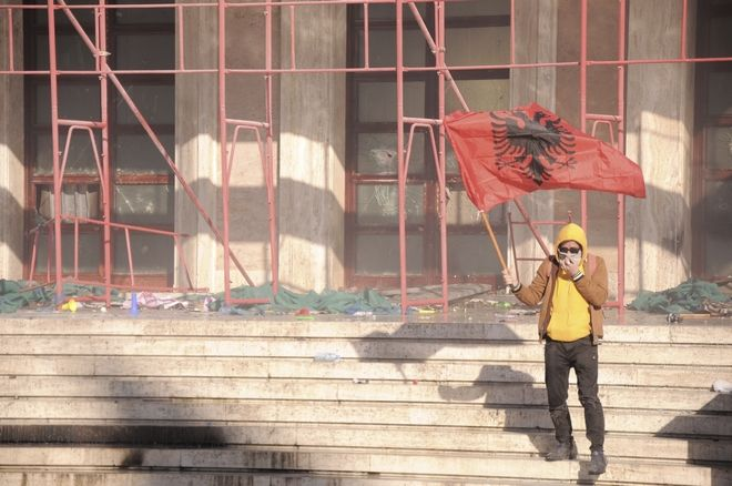 Διαδηλωτής κρατά τη σημαία της χώρας