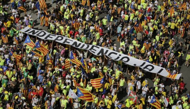 People hold a banner reading 'Independence now' as they gather for a rally to show support for a Catalan independent nation and the right to vote in a controversial referendum that has been banned by Spain. Monday's rally falls on National Catalonia Day, which is celebrated annually. But this year, it comes amid deep social and political division over the Oct. 1 vote. (AP Photo/Emilio Morenatti)