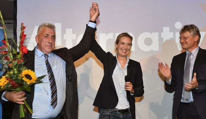 AfD top candidate Alice Weidel, center, gets flowers during the election party of the nationalist 'Alternative for Germany', AfD, in Berlin, Germany, Sunday, Sept. 24, 2017, after the polling stations for the German parliament elections had been closed. (AP Photo/Martin Meissner)