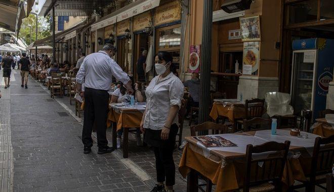 Σερβιτόρα έξω από ταβέρνα στο κέντρο της Αθήνας