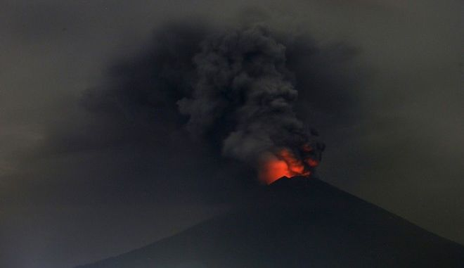 A view of Mount Agung volcano erupting in Karangasem, Bali, Indonesia, Monday, Nov. 27, 2017. Indonesia authorities raised the alert for the rumbling volcano to highest level on Monday and closed the international airport on tourist island of Bali stranding thousands of travelers. (AP Photo/Firdia Lisnawati)