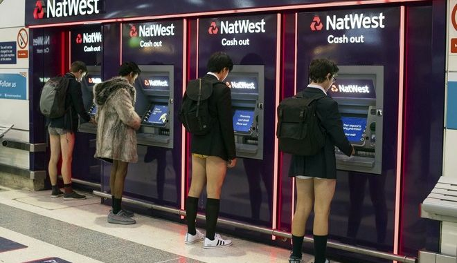 Men use cash machines at Liverpool Street station as they take part in No Trousers on the Tube day, in London, Sunday, Jan. 7, 2018. (Dominic Lipinski/PA via AP)
