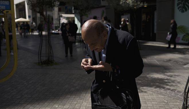 An elderly man checks change in his hand in central Athens, Thursday, March 8, 2018. Several thousand pensioners took part in the rally against another planned round of bailout-related cuts next year. Despite Greece's modest return to growth after years of financial crisis, the cuts are expect to worsen the country's poverty levels. (AP Photo/Petros Giannakouris)