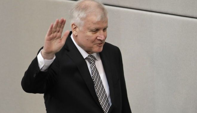 German Interior Minister Horst Seehofer takes the oath of office after the new government was appointed after German Chancellor Angela Merkel was elected for a fourth term as chancellor in the German parliament Bundestag in Berlin, Germany, Wednesday, March 14, 2018. (AP Photo/Michael Sohn)