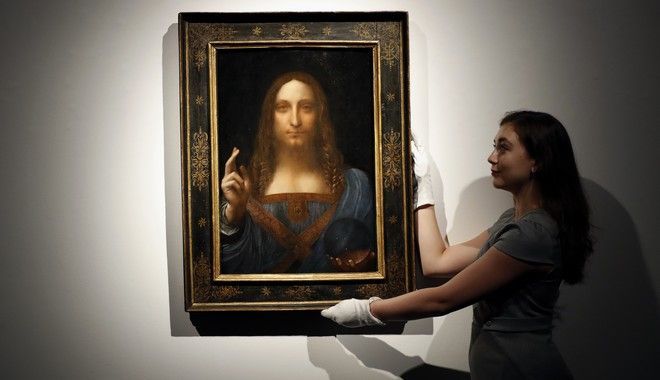 FILE- In this Oct. 24, 2017 file photo, an employee poses with Leonardo da Vinci's