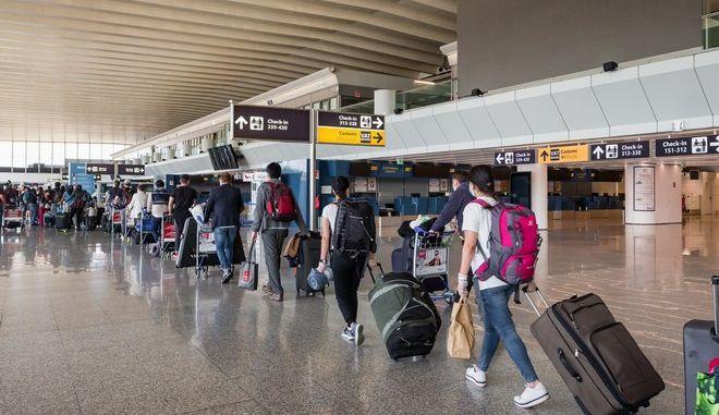 Ταξιδιώτες με μάσκες σε αεροδρόμιο