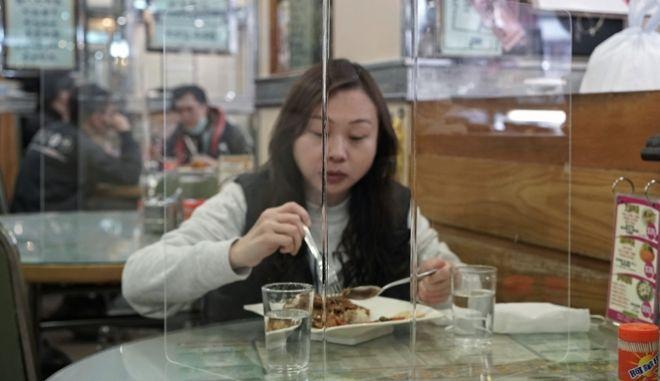 Γυναίκα σε εστιατόριο του Χονγκ Κονγκ, τρώει προστατευμένη από πλαστικό περίβλημα που την απομονώνει από τους υπόλοιπους πελάτες.