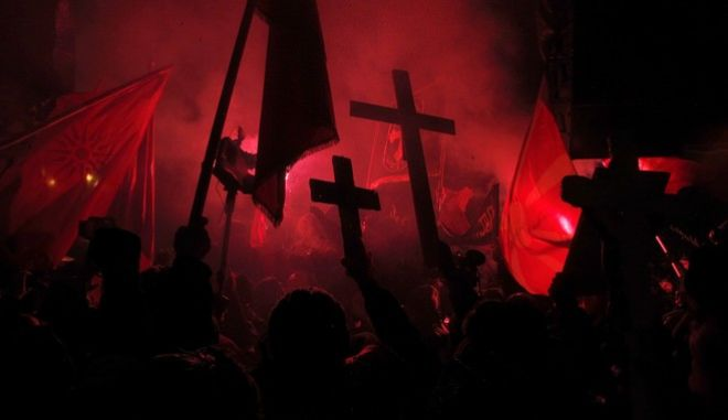Protestors carry crosses and light torches during a protest against the change of the country's constitutional name, in front of the Parliament building in Skopje, Macedonia, Tuesday, Feb. 27, 2018. Several thousand protestors have gathered in front of Macedonia's parliament to demand that the government call off talks with neighbor Greece on a decades-long name dispute. (AP Photo/Boris Grdanoski)