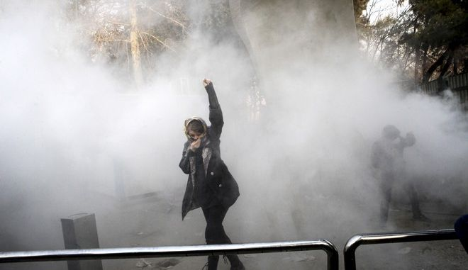 In this photo taken by an individual not employed by the Associated Press and obtained by the AP outside Iran, a university student attends a protest inside Tehran University while a smoke grenade is thrown by anti-riot Iranian police, in Tehran, Iran, Saturday, Dec. 30, 2017. A wave of spontaneous protests over Iran's weak economy swept into Tehran on Saturday, with college students and others chanting against the government just hours after hard-liners held their own rally in support of the Islamic Republic's clerical establishment. (AP Photo)