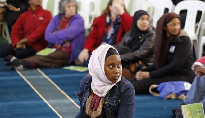 A woman listens inside the Open Mosque, as she and other woman share the same area with men in Cape Town, South Africa, Friday, Sept. 19, 2014. The Open Mosque was founded by Dr. Taj Hargey and is based on gender equality and non-sectarian Islamic rules - Christians and people from other religions are welcomed and woman share the same area for prayers as men inside the mosque. Hargey claims it is the first of its kind in South Africa. (AP Photo/Schalk van Zuydam)