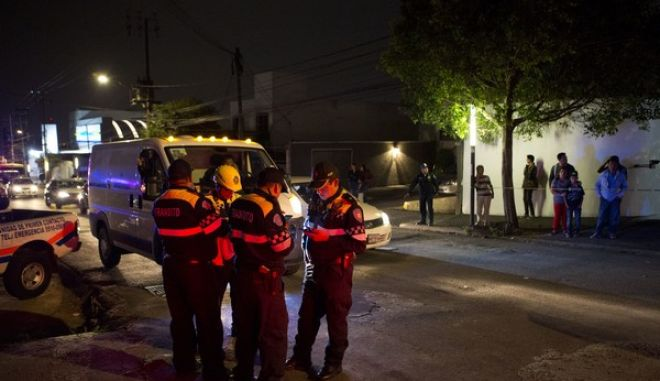 Residents look on as transit police confer outside the scene where a parking garage under construction collapsed in Mexico City, Monday, April 10, 2017. Part of building under construction collapsed on Monday, trapping workers underneath concrete beams and killing several, officials said. (AP Photo/Rebecca Blackwell)