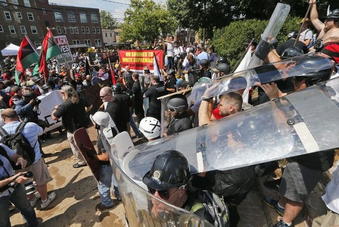 White nationalist demonstrators use shields as they clash with counter demonstrators at the entrance to Lee Park in Charlottesville, Va., Saturday, Aug. 12, 2017.   Hundreds of people chanted, threw punches, hurled water bottles and unleashed chemical sprays on each other Saturday after violence erupted at a white nationalist rally in Virginia. At least one person was arrested.  (AP Photo/Steve Helber)