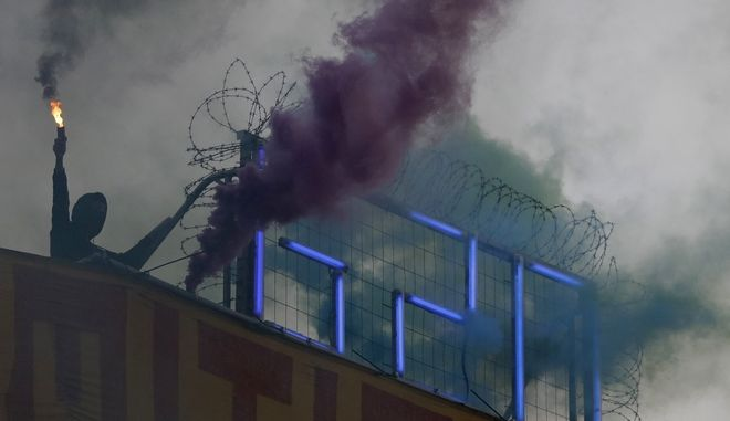 A demonstrator lights smoke markers on top of the Rote Flora squat during a protest against the G-20 summit in Hamburg, northern Germany, Wednesday, July 5, 2017. The leaders of the group of 20 meet July 7 and 8. (AP Photo/Matthias Schrader)