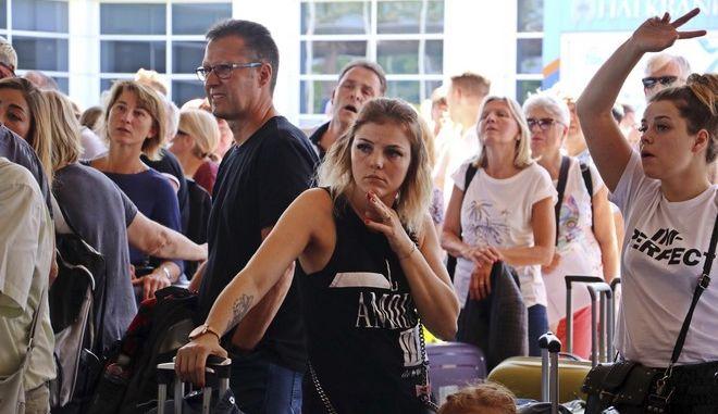 Ταλαιπωρημένοι επιβάτες της Thomas Cook περιμένουν σε ουρά στο αεροδρόμιο της Αττάλειας να ενημερωθούν για την πτήση τους