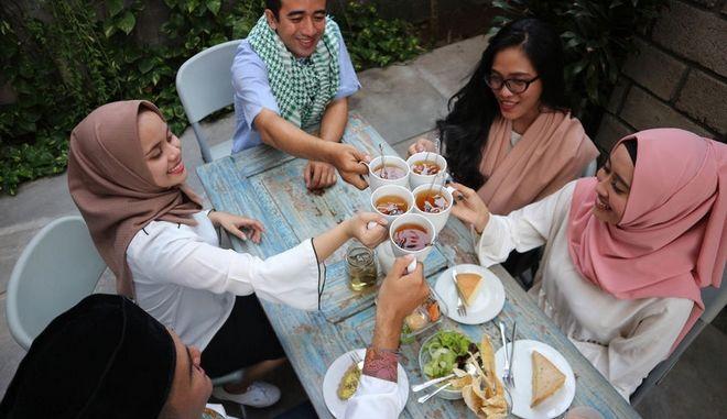 Γυναίκες και άντρες τρώνε μαζί.