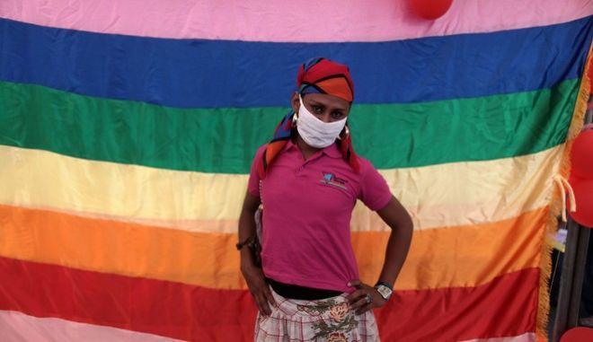 Τρανς γυναίκα μπροστά από τη σημαία ΛΟΑΚΤΙ+