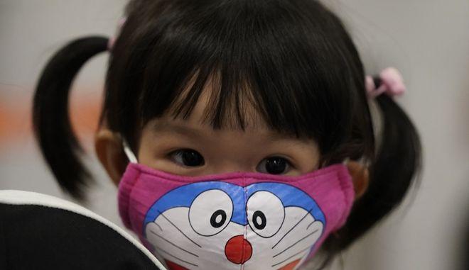 Κοριτσάκι από την Κίνα που φορά μάσκα προσώπου