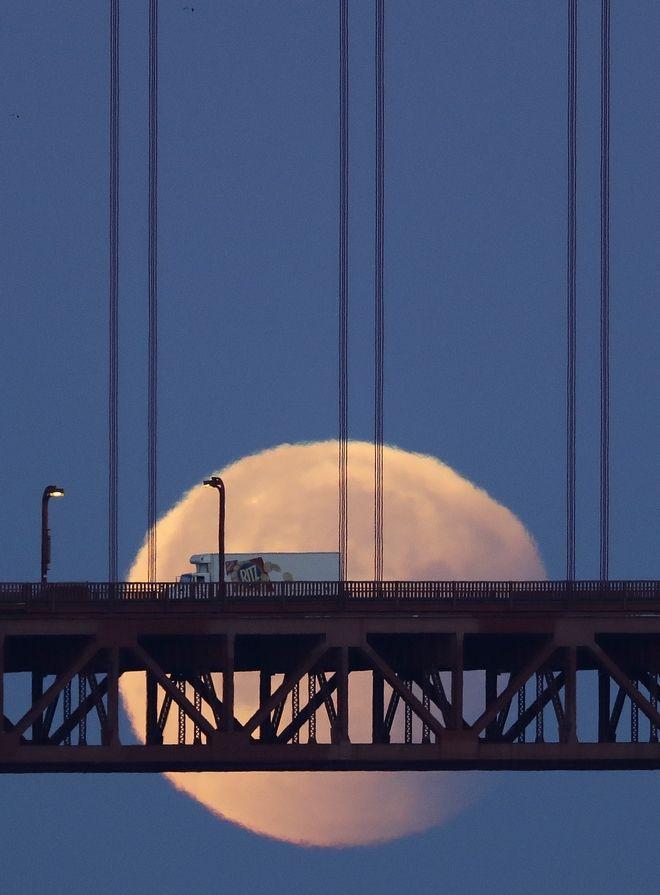 A super blue blood moon sets behind the Golden Gate Bridge Wednesday, Jan. 31, 2018, in San Francisco.(AP Photo/Marcio Jose Sanchez)