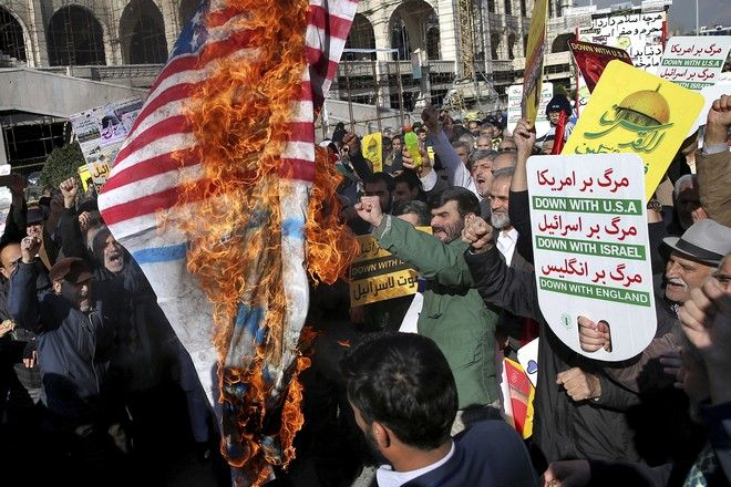 Iranian worshippers burn representation of US flag in a rally after Friday prayer in Tehran, Iran, Friday, Dec. 8, 2017. Hundreds of Iranian worshippers have staged a rally to show their anger against the U.S. President Donald Trump administration's recognition this week of Jerusalem as the capital of Israel. (AP Photo/Ebrahim Noroozi)