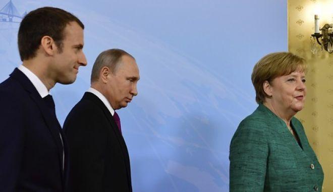 Οι πρόεδροι Γαλλίας και Ρωσίας Εμανουέλ Μακρόν και Βλαντίμιρ Πούτιν και η Γερμανίδα καγκελάριος Άνγκελα Μέρκελ σε συνάντησή τους στο Αμβούργο τον Ιούλιο του 2017