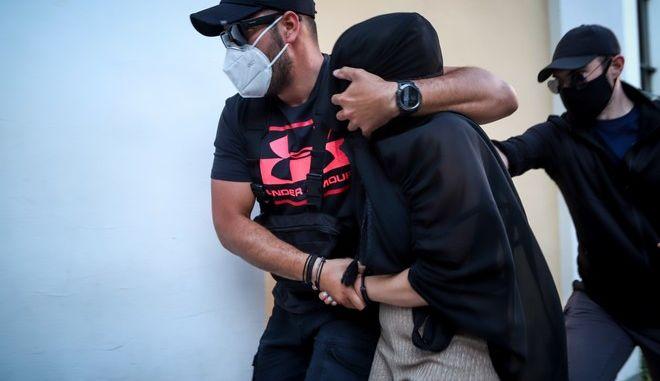 Η 35χρονη η οποία κατηγορείται για την επίθεση με βιτριόλι οδηγείται από αστυνομικούς στον ανακριτή.