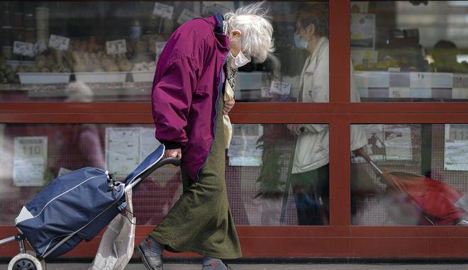 Ηλικιωμένη με μάσκα περπατά στην πόλη (φωτογραφία αρχείου)