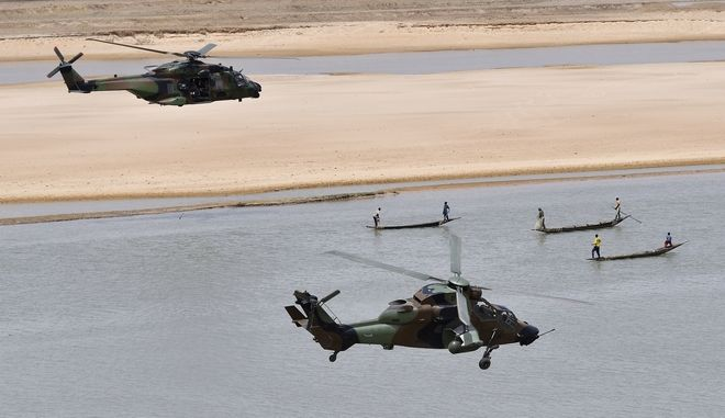 French President Emmanuel Macron flies over Gao in a military helicopter, left, as he visits the troops of Operation Barkhane, France's largest overseas military operation, in Gao, northern Mali, Friday, May 19, 2017. On his first official trip outside Europe, new French President Emmanuel Macron is highlighting his determination to crush extremism with a visit to French-led military forces combating jihadist groups in West Africa. (Christophe Petit Tesson, Pool via AP)