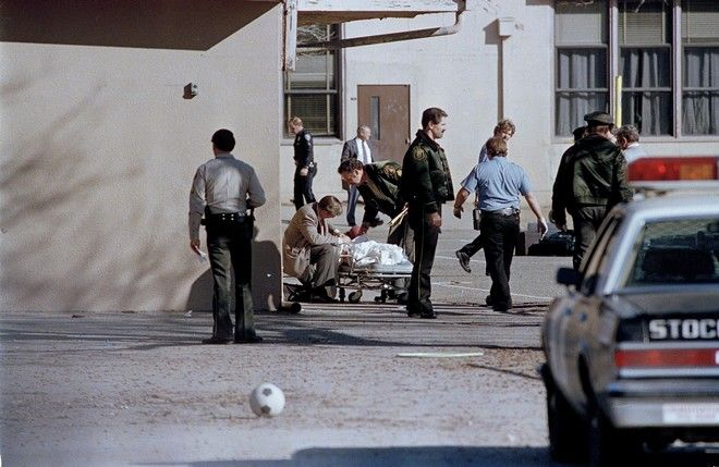 Police examine the covered body of a shooting victim at the Cleveland Elementary School in Stockton, Calif., Jan. 17, 1989. A gunman shot and killed five students and wounded 30 others, then killed himself. Police identified the gunman as Patrick E. West, 24, of Lodi, Calif. (AP Photo/Walt Zeboski)