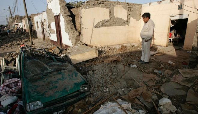 A man watches a car destroyed by an earthquake in Pisco, Peru, Friday, Aug. 17, 2007. Peru's fire department said late Thursday the death toll from the magnitude-8 quake that devastated the southern coast had risen to 510, and rescuers were still digging through rubble from collapsed adobe homes in cities and hamlets.(AP Photo/Victor R. Caivano)