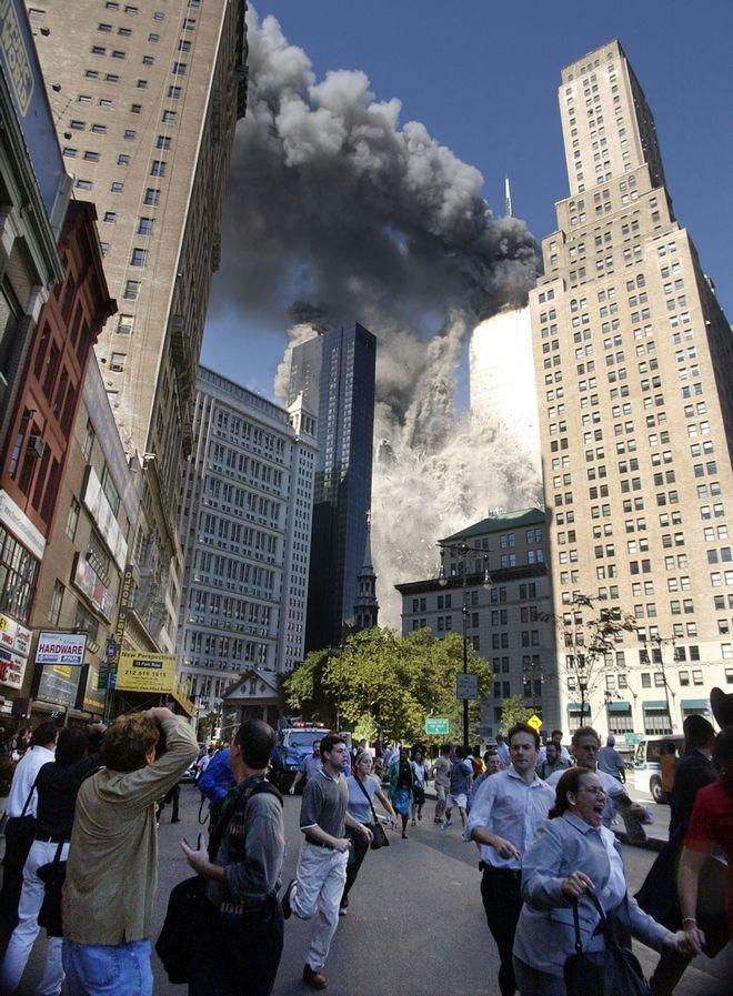 Άνθρωποι τρέχουν μακριά από τους δίδυμους Πύργους που καταρρέουν