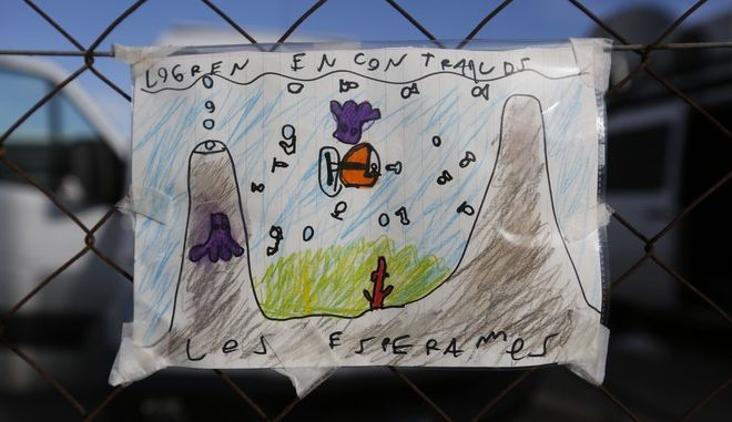 """In this Sunday, Nov. 19, 2017 photo, a child's drawing with the Spanish """"Find them, we wait for them,"""" referring to the crew of a missing submarine, hangs on a fence at the naval base in Mar del Plata, Argentina. An apparent explosion occurred near the time and place an Argentine submarine went missing, the country's navy reported Thursday, Nov. 23, prompting relatives of its 44 crew members to burst into tears and some to say they had lost hope of a rescue.  (AP Photo/Vicente Robles)"""