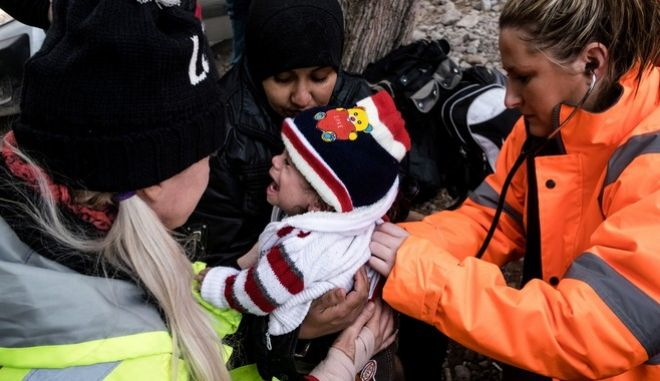 Paramedics give first aid to a Syrian child after a boat with refugees and migrants arrive in a beach near Skala Sikamineas village in Lesbos island, Greece on November 16, 2015.