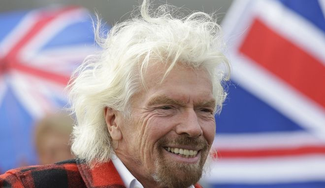 FILE - In this Monday, March 27, 2017, file photo, Richard Branson, founder of Virgin Atlantic and the Virgin Group, smiles after he arrived on a flight from London to Seattle, at Seattle-Tacoma International Airport in Seattle. Bransons prolific Virgin brand has spanned a broad range of businesses, including record stores, banks, phones, airlines and spaceships. Hes now trying to help Sprint revitalize its Virgin Mobile brand by transforming it into an iPhone-only carrier. He tells The Associated Press that Virgin is synonymous with really good quality, as is Apple, giving Virgin a real chance to break in. (AP Photo/Ted S. Warren, File)