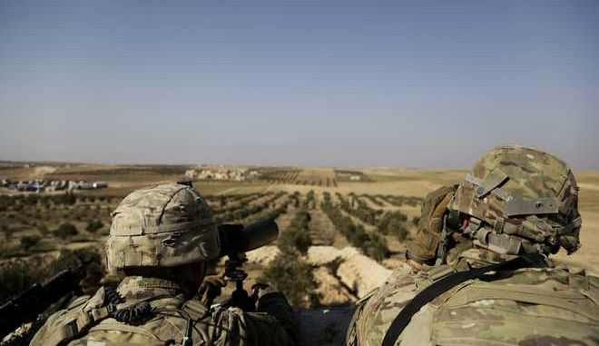 FILE - This Wednesday, Feb. 7, 2018 file photo, shows American troops looking  toward the border with Turkey from a small outpost near the town of Manbij, northern Syria. As Syrian troops and their allies push toward final victory and the battle against Islamic State militants draws to an end, new fronts are opening up, threatening an even broader confrontation. The U.S., Israel and Turkey all have deepened their involvement, seeking to protect their interests in the new Syria order. (AP Photo/Susannah George, File)