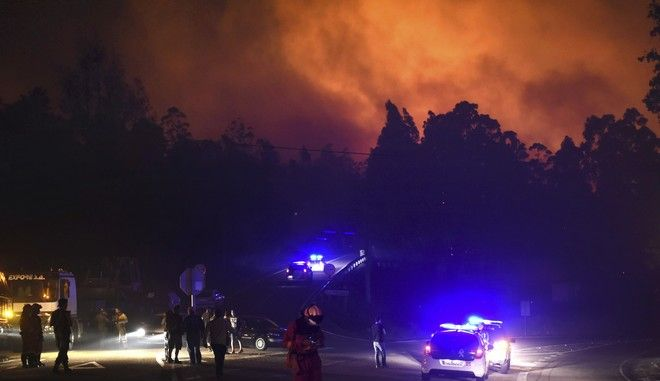 Police cars block the area as emergency vehicles responded to a wild fire in As Neves, Pontevedra, in the northwestern Spanish region of Galicia, Spain on Monday, Oct. 16, 2017. Authorities in Portugal and Spain say that nine people died over the weekend in hundreds of wildfires fanned by strong winds caused by a hurricane. Three people, two of whom were trapped in a car, were killed as a result of more than 130 blazes reported in different areas, officials said. (AP Photo/Alba Sotelo)