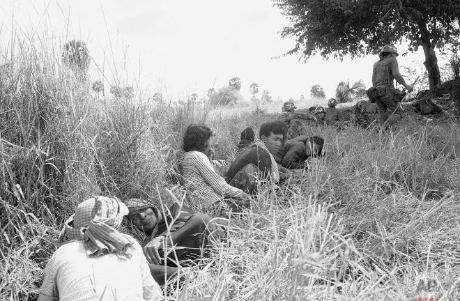 A Cambodian family huddles next to a paddy dike near South Vietnamese soldiers, background. They left their nearby home when a firefight broke out in the area, about 50 miles northeast of Phnom Penh on Jan. 2, 1971. (AP Photo/Nick Ut)