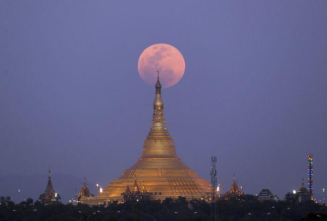 The moon rises behind the Uppatasanti Pagoda seen from Naypyitaw, Myanmar, Wednesday, Jan. 31, 2018. (AP Photo/Aung Shine Oo)