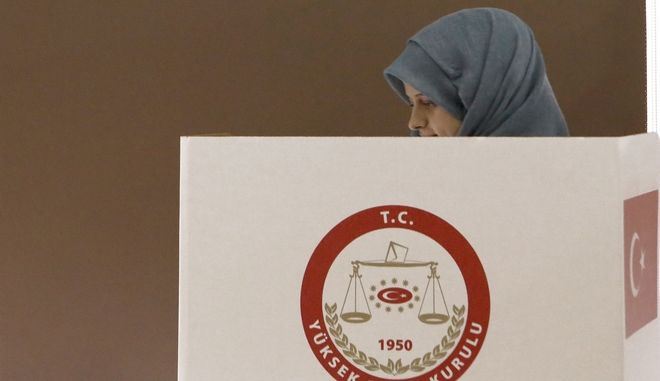 A Turkish woman living in the breakaway north of ethnically divided Cyprus, stands behind a polling booth as she casts her vote in a referendum on expanding presidential powers in Turkey, in the Turkish Cypriot breakaway part of divided capital Nicosia, Wednesday, April 5, 2017.   Turkish officials have said as many as 100,000 people living in the breakaway north of Cyprus are eligible to vote early in the Turkish referendum. (AP Photo/Petros Karadjias)