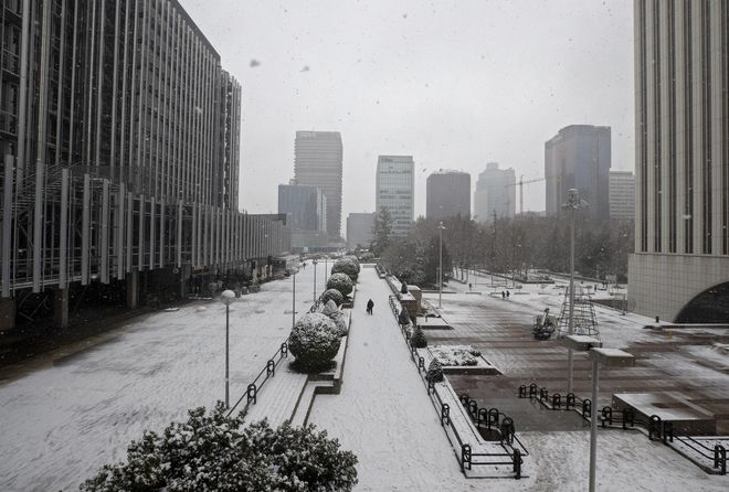 A man walks in the business district during a snowfall in Madrid, Spain, Friday, Jan. 8, 2021. Spain is on high alert Friday as a cold snap is covering much of the country with snow, causing disruptions in road, sea and air traffic while authorities warn that the worst may still be coming over the weekend. (AP Photo/Paul White)