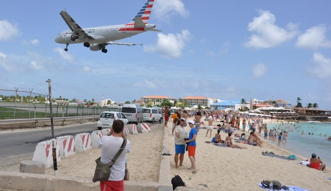 A plane lands at the Princess Juliana International Airport as beachgoers watch in Philipsburg, St. Maarten, a Dutch Caribbean territory, Thursday, July 13, 2017. On Wednesday, a New Zealand tourist was killed by the blast from a jetliner taking off when she was knocked into a wall as she tried to cling to a fence to feel the blast. (AP Photo/Judy Fitzpatrick)