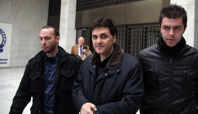 """Ο Αγγελος Φιλιππίδης οδηγείται από την ΓΑΔΑ στα Δικαστήρια μετά την σύλληψή του το πρωΐ της Τετάρτης 5 Φεβρουαρίου 2014,  στο αεροδρόμιο """"Ελευθέριος Βενιζέλος"""", όπου έφτασε με πτήση των τουρκικών αερογραμμών. Η άφιξη του καταζητούμενου επιτεύχθηκε κατόπιν συνεννόησης του ελληνικού υπουργείου Εξωτερικών με τις τουρκικές αρχές.  (EUROKINISSI/ΑΛΕΞΑΝΔΡΟΣ ΖΩΝΤΑΝΟΣ)"""