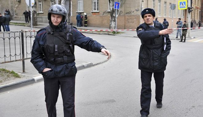 Police officers cordon a street after an explosion occurred in southern Russian city of Rostov-on-Don, Thursday, April 6, 2017. A man was seriously injured when he inadvertently detonated an explosive device in Rostov-on-Don. Thursday's explosion occurred when the man touched a flashlight hidden in a bag left near a school building, according to the National Guard. Russian law enforcement agencies have launched a manhunt for those responsible.(AP Photo)