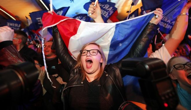 Supporters of far-right leader and candidate for the 2017 French presidential election, Marine Le Pen, celebrate after exit poll results of the first round of the presidential election are announced at election day headquarters in Henin-Beaumont, northern France, Sunday, April 23, 2017. Polling agency projections show far-right leader Marine Le Pen and centrist Emmanuel Macron leading in the first-round French presidential election. (AP Photo/Frank Augstein)