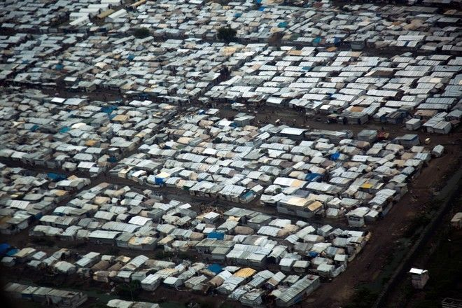 14 June 2016. Malakal: Aerial view of Protection of Civilians (PoC) site in Malakal, South Sudan.  The rainy season started and made the living conditions very difficult for the displaced people in one of the most crowded PoC in South Sudan. In some areas, the density in this camp is around 9 square meters per person, which is highly below the UN standards (30).  People are facing health risks such malaria and cholera due to the lack of good draining infrastructures. 32,000 people are currently living in this PoC that faced on of the most violent episodes in the South Sudanese civil war.   Fighting between elements of the Shilluk and Dinka communities erupted in the Malakal PoC on February 17. UN reports confirmed that armed men in Sudan People's Liberation Army (SPLA) uniforms entered the UN camp and fired on civilians, looting and burning tents. At least 18 people were killed and more than 90 wounded. After the clashes, Dinka families (approximately 4,000 people) fled outside the PoC and sought refugee into Malakal town, while about 26,000 Nuer and Shilluk IDPs, mostly women and children, sought refugee in the former PoC. Photo by Albert Gonzalez Farran - MSF