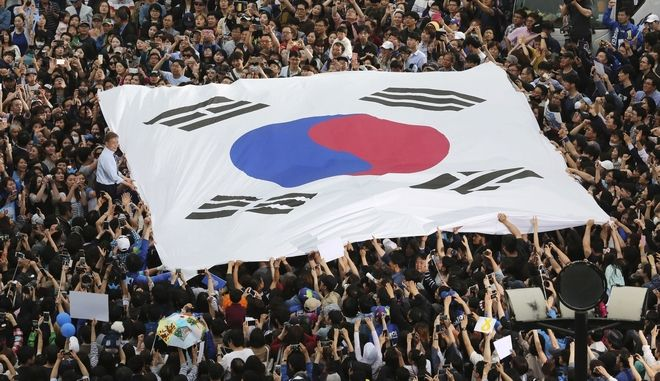 South Korea's presidential candidate Moon Jae-in, left, wearing a blue shirt, from the Democratic Party holds a national flag during a presidential election campaign in Goyang, South Korea, Thursday, May 4, 2017. South Koreans began early voting Thursday in the election to replace ousted President Park Geun-hye. (AP Photo/Ahn Young-joon)