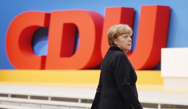 German Chancellor Angela Merkel walks past the party logo during a party convention of the Christian Democrats (CDU) in Karlsruhe, Germany, Monday, Dec. 14, 2015. (AP Photo/Michael Probst)